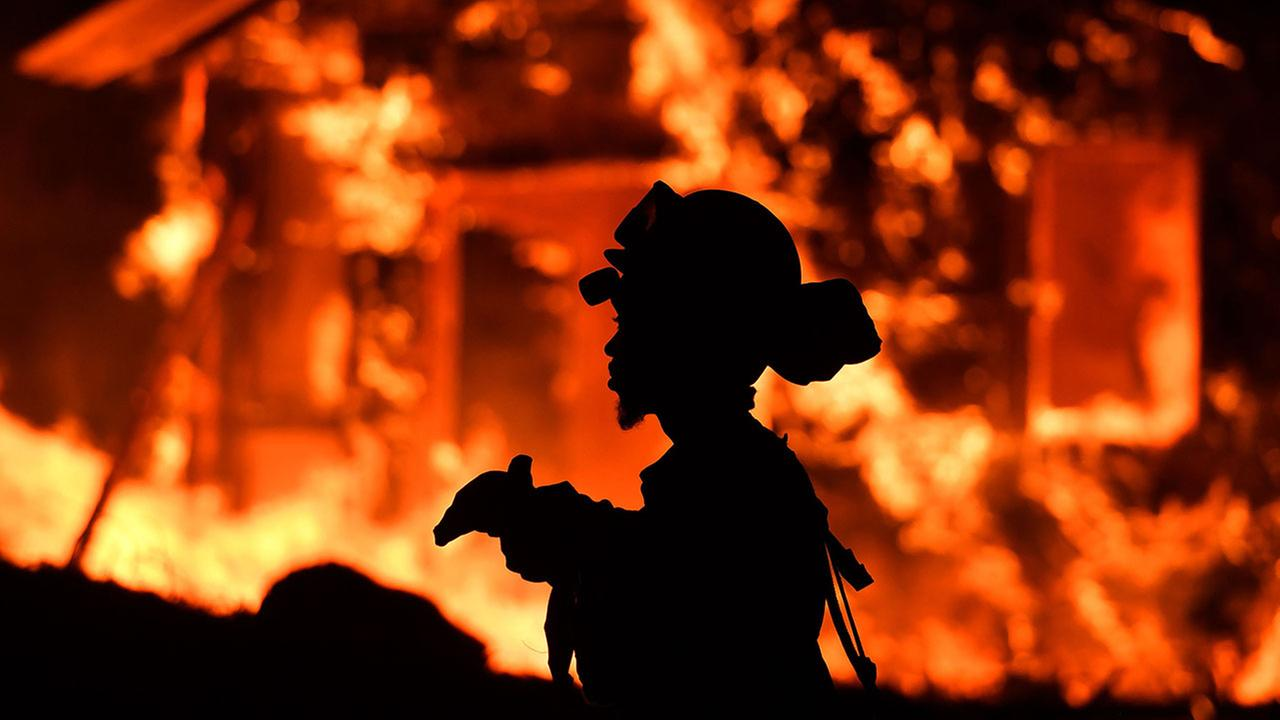 An inmate firefighter monitors flames as a house burns in the Napa wine region in California on October 9, 2017, as multiple wind-driven fires continue to whip through the region. JOSH EDELSON/AFP/Getty Images