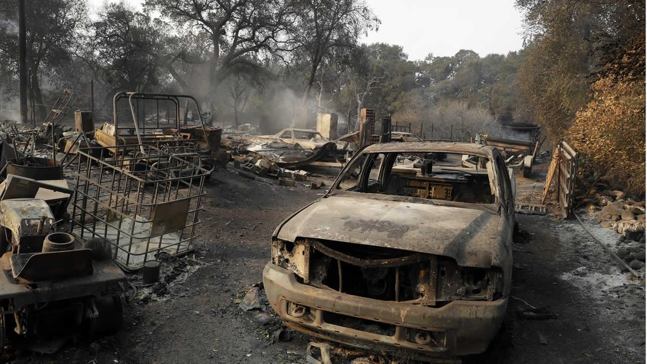 Burned out vehicles are parked in front of a fire-ravaged home Monday, Oct. 9, 2017, in Napa, Calif. (AP Photo/Marcio Jose Sanchez)