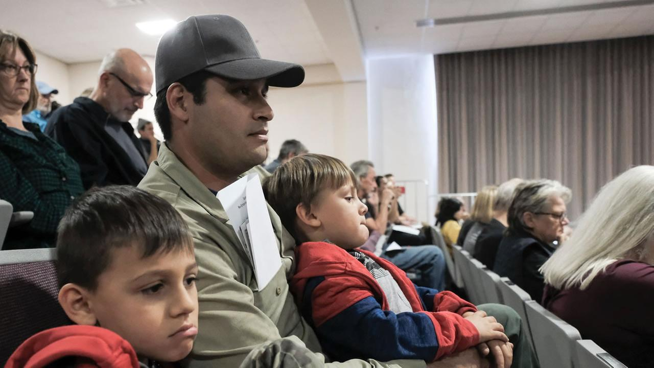 A family slumps in their seats during a meeting in Sonoma County, Calif. after the North Bay fires on Thursday, Oct. 19, 2017.