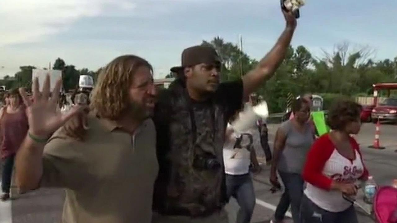 Black and white man march together in Missouri protest