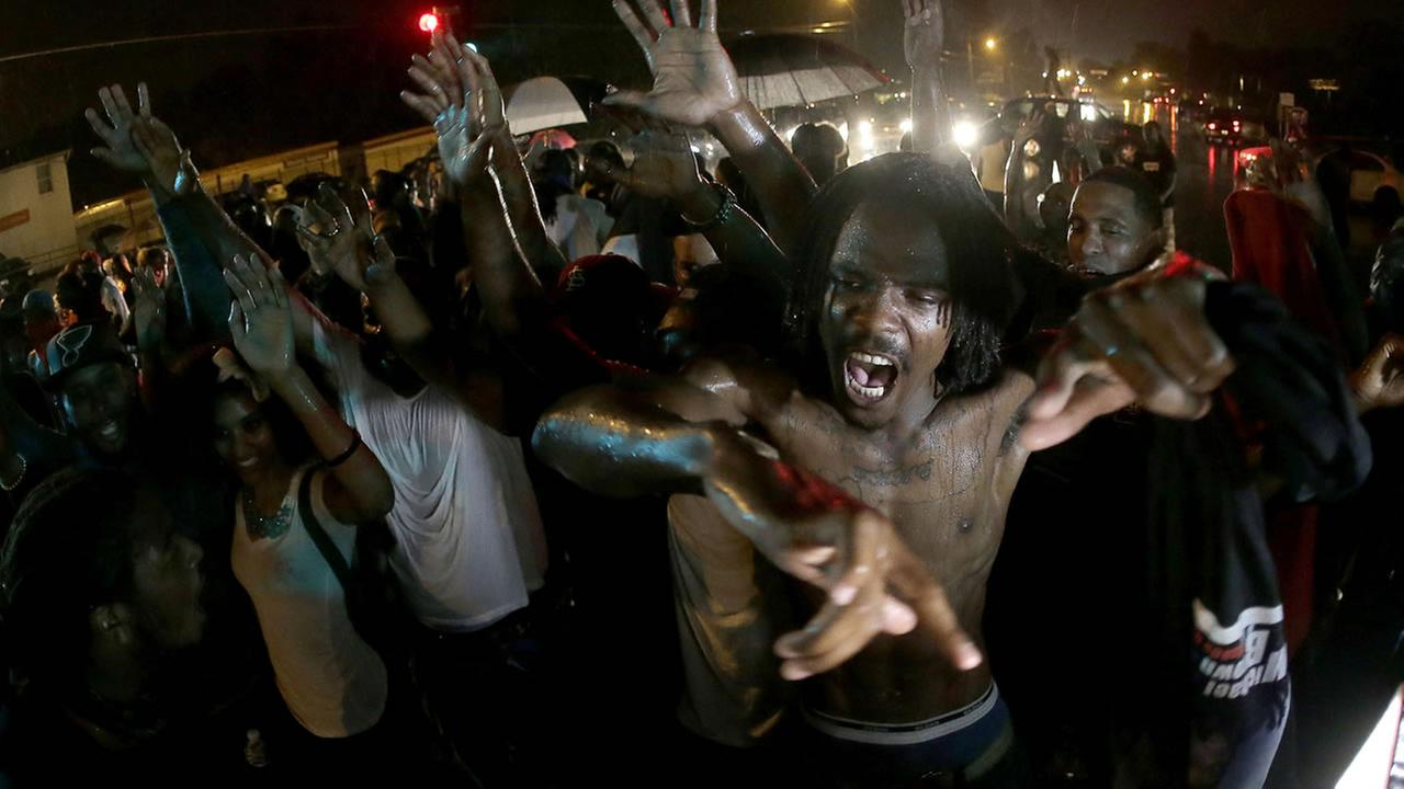 People defy a curfew Sunday, Aug. 17, 2014, before smoke and tear gas was fired to disperse a crowd protesting the shooting of teenager Michael Brown (AP Photo/Charlie Riedel)