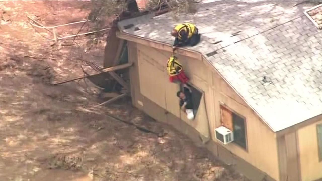 Rescuers help people trapped inside their homes by flooding in Arizona.