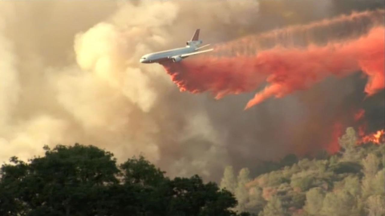 A plane drops fire retardant on the fire thats scorched more than 600 acres in Oakhurst, near Yosemite.