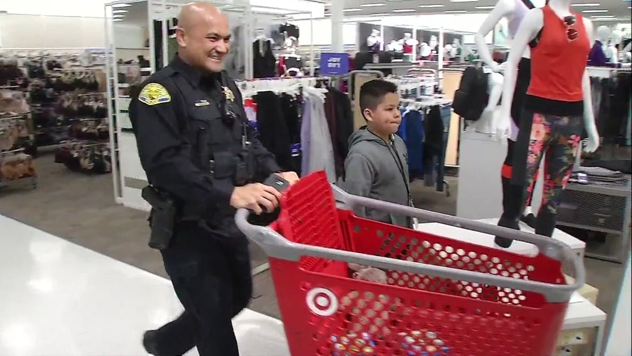A police officer shops with a child at Target in San Jose, Calif. on Wednesday, Dec. 6, 2017.
