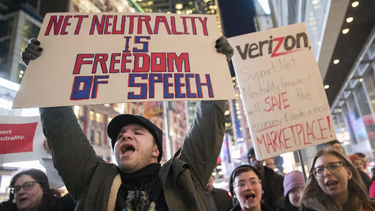FILE - In this Thursday, Dec. 7, 2017, file photo, demonstrators rally in support of net neutrality outside a Verizon store in New York.  (AP Photo/Mary Altaffer, File)