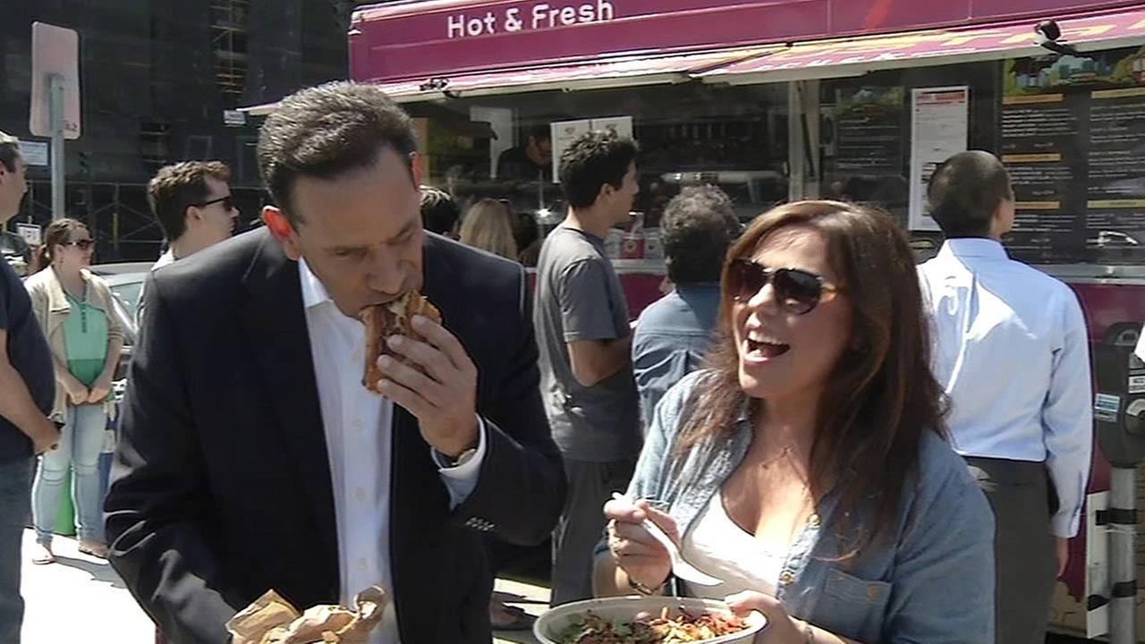 ABC7 News anchor Larry Beil and Rachael Ray eating food from food trucks