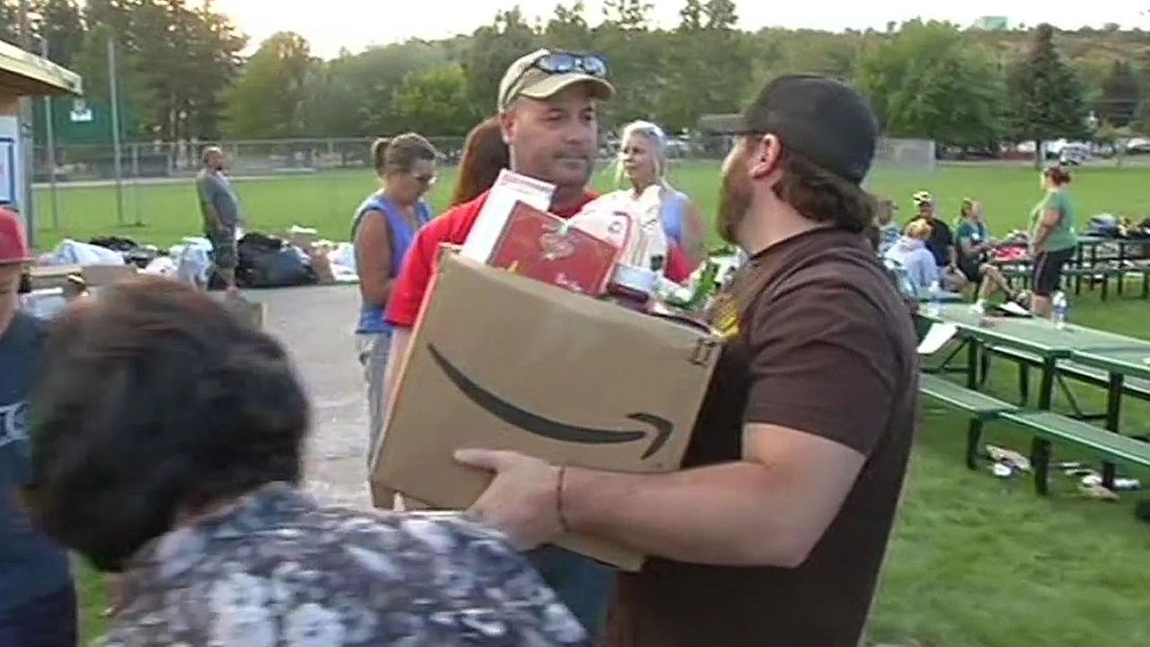 a fire victim carries a box of donations