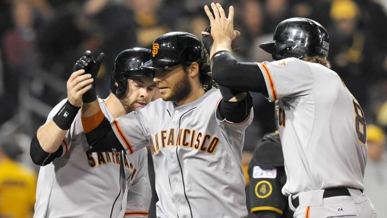 San Francisco Giants Brandon Crawford, center, is greeted by teammates Brandon Belt, left, and Hunter Pence right, after hitting a grand slam against the Pittsburgh Pirates.
