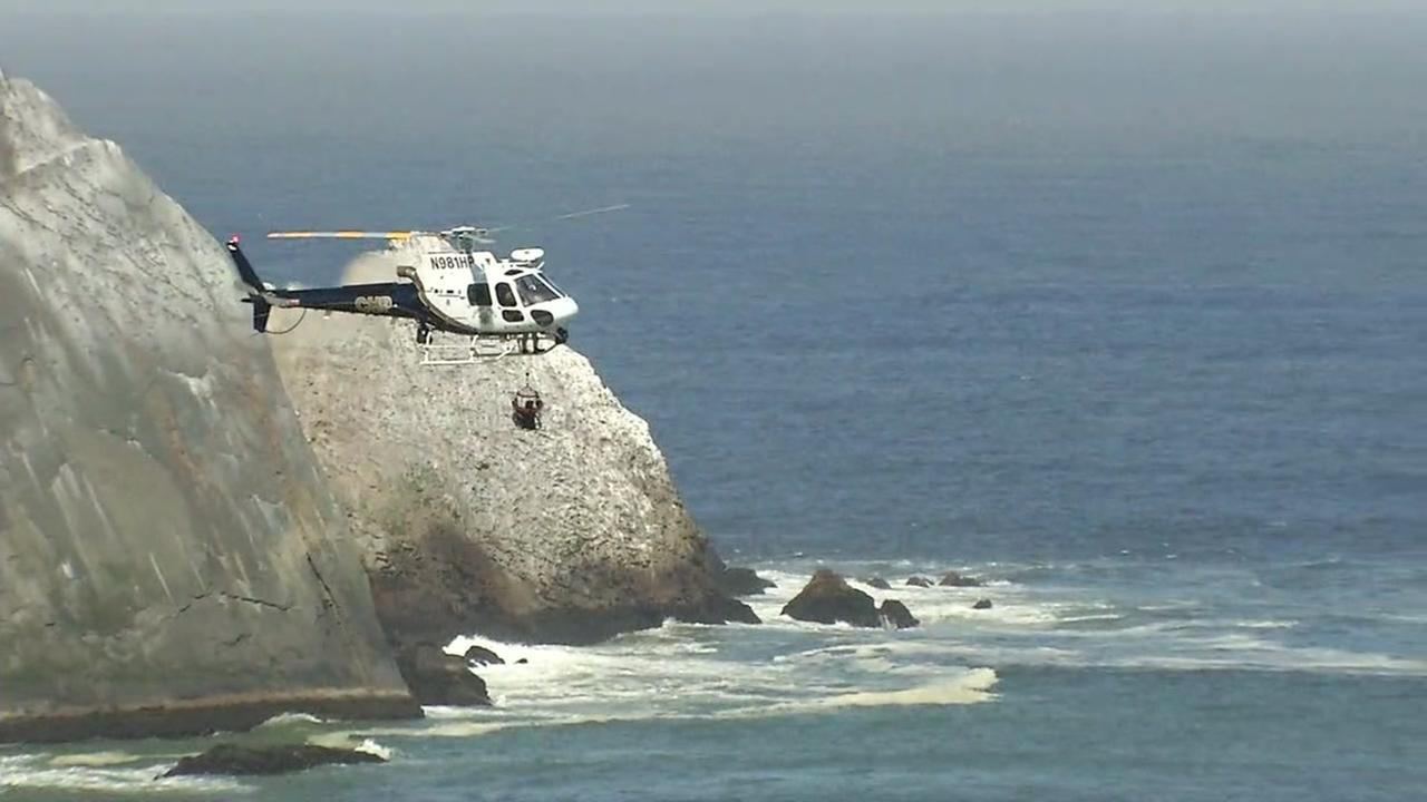Hikers are seen being airlifted by a CHP helicopter after being rescued from a cliff in Pacifica, Calif. on Saturday, June 16, 2018.