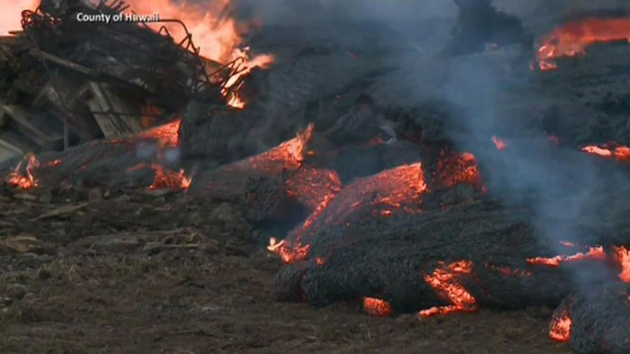 Lava flowing from the Kilauea volcano is about 100 feet away from a rural house on Hawaiis Big Island.