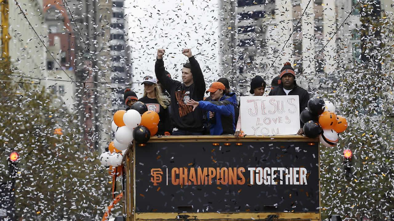 Giants catcher Buster Posey waves to fans as he rides with pitcher Santiago Casilla during the baseball teams 2014 World Series victory parade in SF on Oct. 31, 2014. (AP Photo)