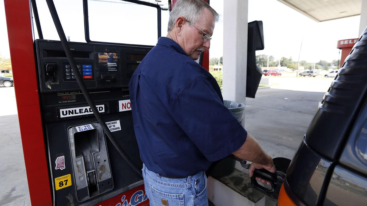 In this Sept. 24, 2014 photo, Foster Gilley, of Chatom, Ala., fills his SUVs tank with $2.92-per-gallon regular gas at Macs Gas in Richland, Miss.(AP Photo/Rogelio V. Solis)