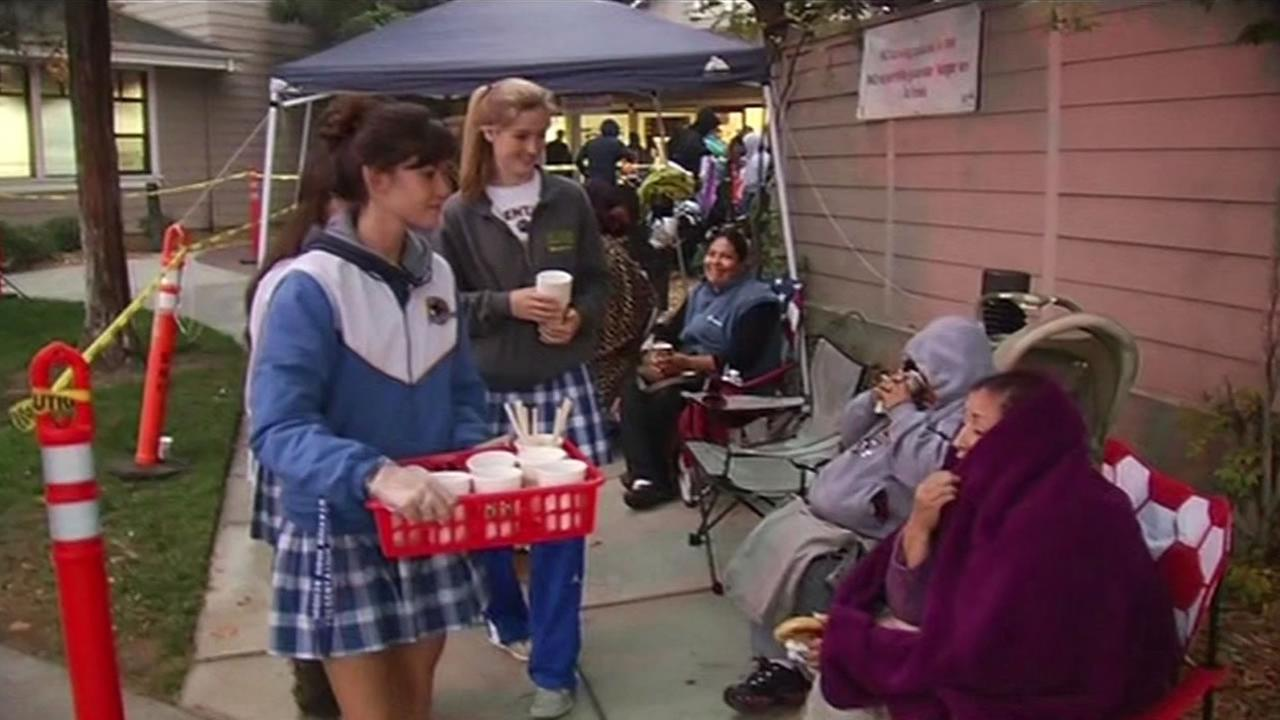 Students at Presentation High School in San Jose deliver bagels and warm drinks to the people lined up to receive holiday food and toys from Sacred Heart Community Service.