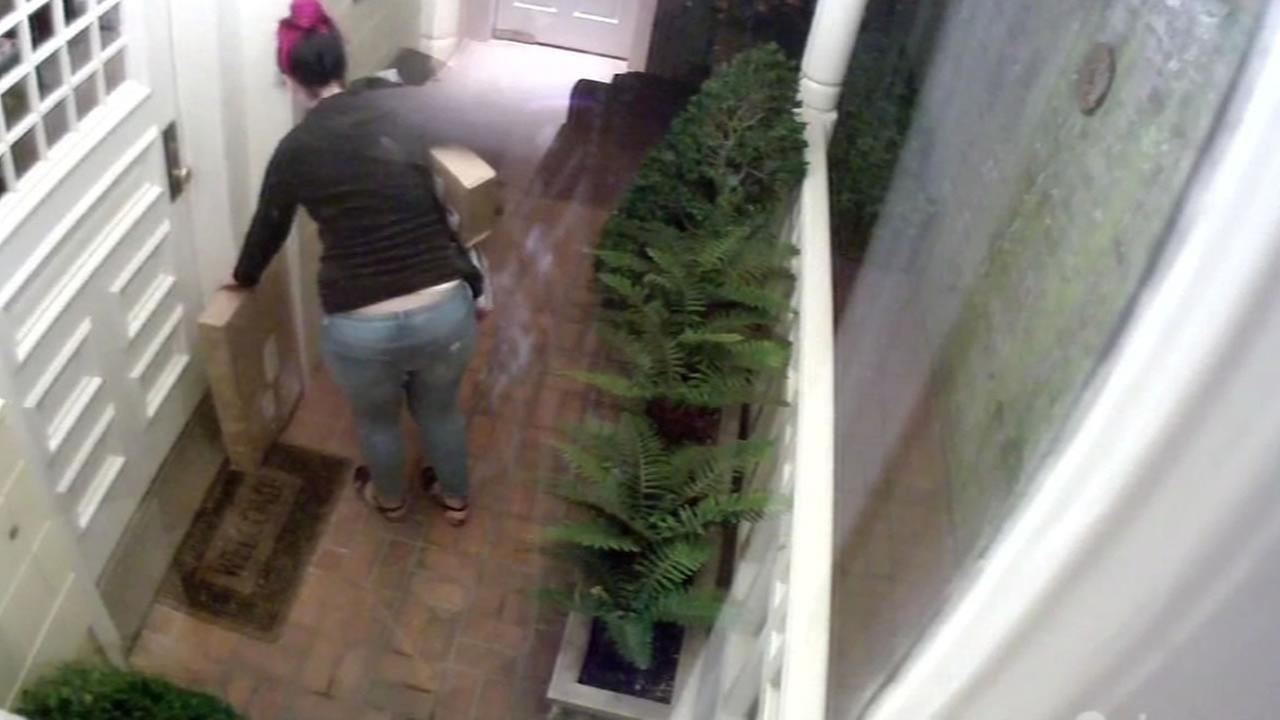 A woman stealing packages off of someones doorstep