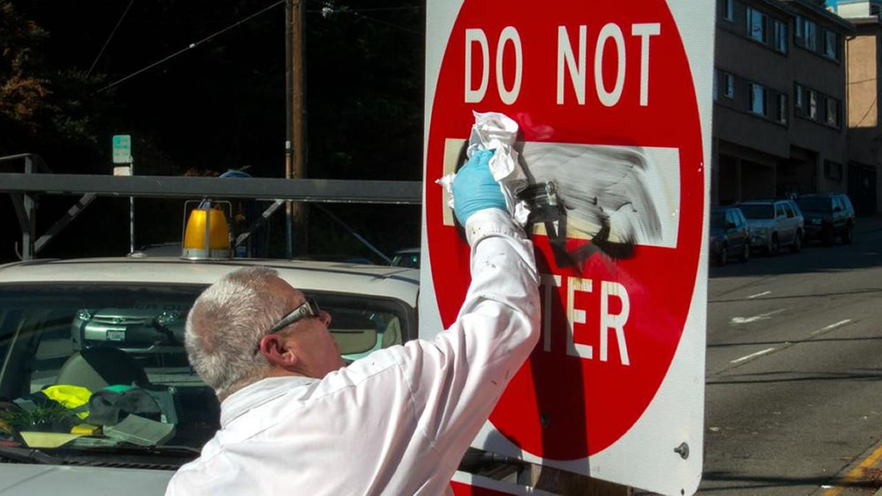 Man cleaning a sign