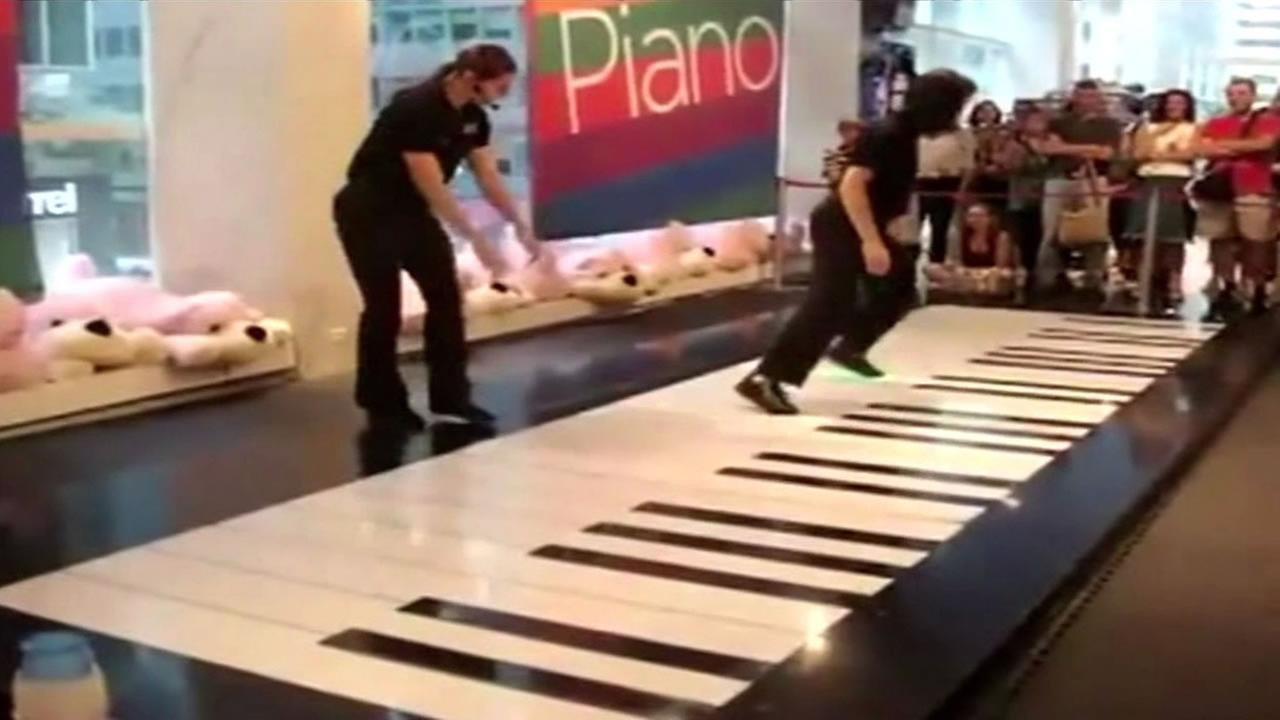 Two employees at the famed FAO Schwarz toy store are entertaining customers by playing the stores famous giant floor piano.