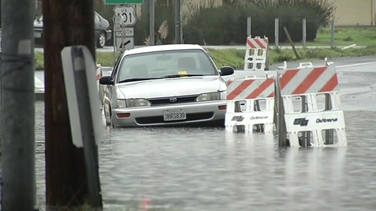 A car is parked in a flooded parking lot in the North Bay