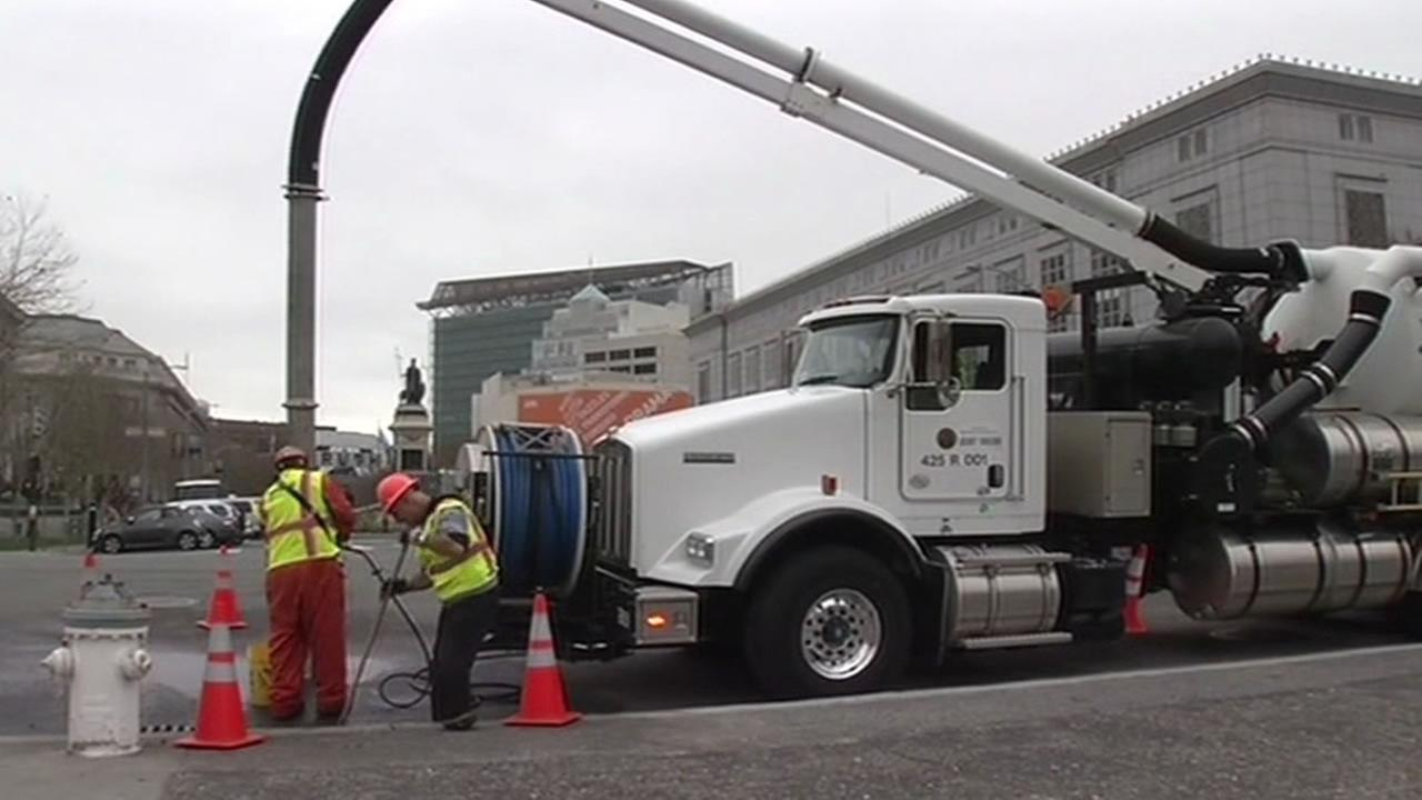 city crews clean streets with big vacuum truck