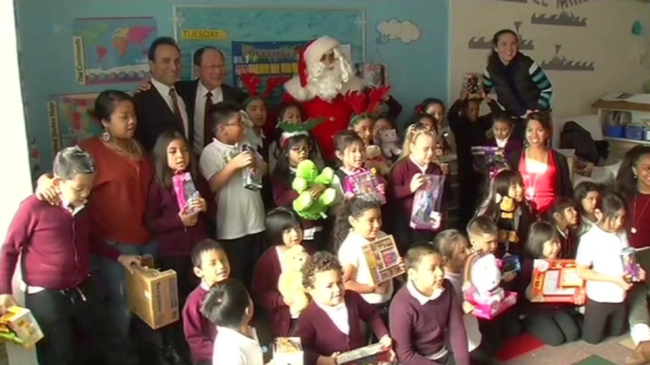 Santa Claus surprises kids with gifts at City Academy in San Francisco