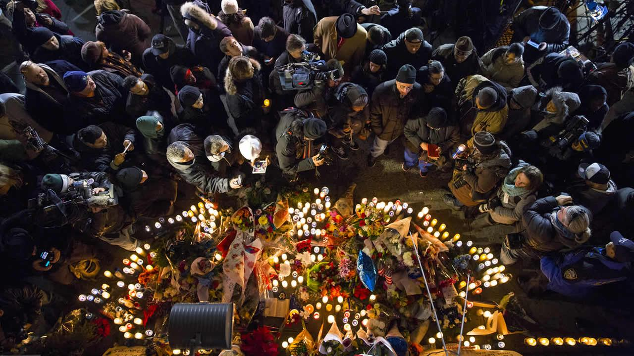 Mourners, members of the media and others gather at a memorial Sunday, Dec. 21, 2014, near the spot where two New York Police Department officers were shot. (AP Photo/Craig Ruttle)