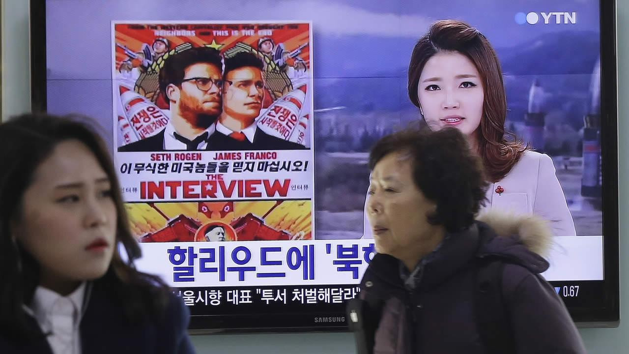 People walk past a TV screen showing a poster of Sony Pictures The Interview in a news report, at the Seoul Railway Station in Seoul, South Korea, Monday, Dec. 22, 2014. (AP Photo)