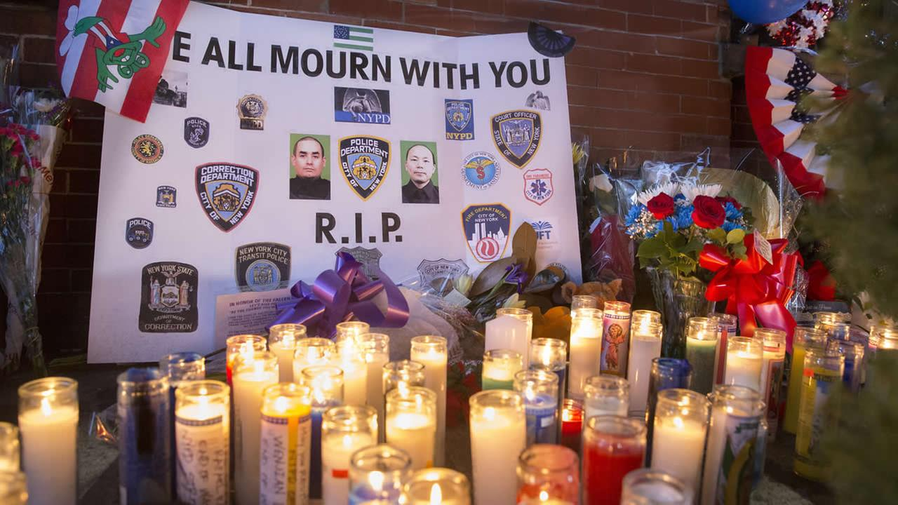 A sign that reads WE ALL MOURN WITH YOU rests against a wall at a makeshift memorial near the site where NYPD officers were murdered in the Brooklyn borough of New York, Monday, Dec. 22, 2014. (AP Photo/John Minchillo)