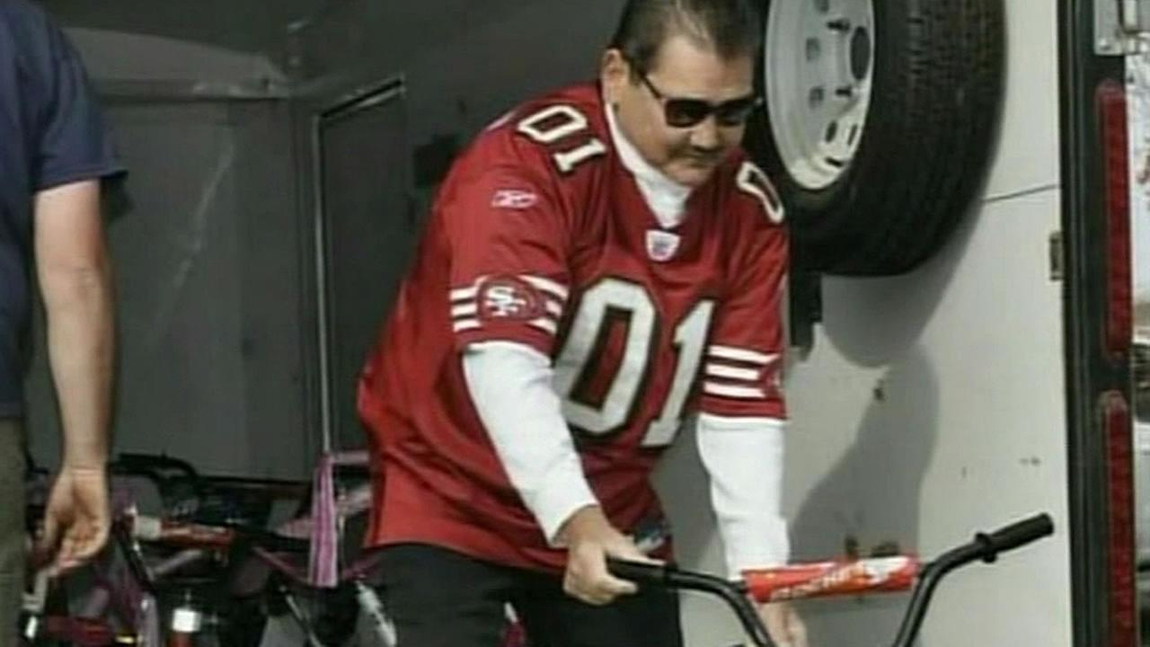 Bill Millard pushes a donated kids bike out of a truck