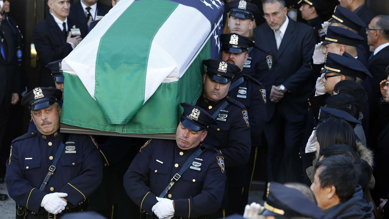 Pallbearers carry the casket of New York City police officer Rafael Ramos following funeral services in Queens, Saturday, Dec. 27, 2014, in New York. (AP Photo/Julio Cortez)