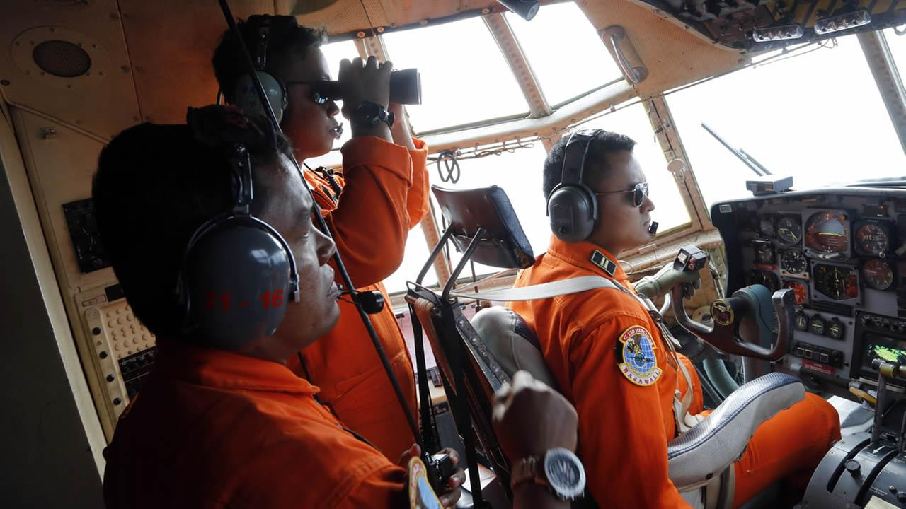 Crew of Indonesian Air Force C-130 airplane of the 31st Air Squadron scan the horizon during a search operation for the missing AirAsia flight 8501 plane. (AP Photo/Dita Alangkara)