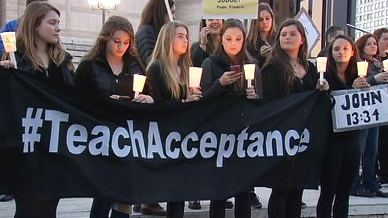 Teens hold candles and a banner saying #TeachAcceptance and a sign saying John 13:34