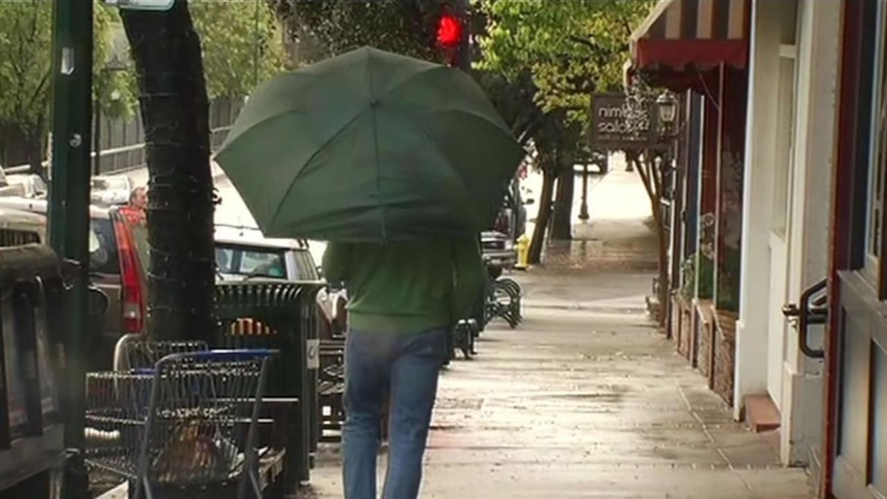 Guy using an umbrella in the rain in Los Gatos.