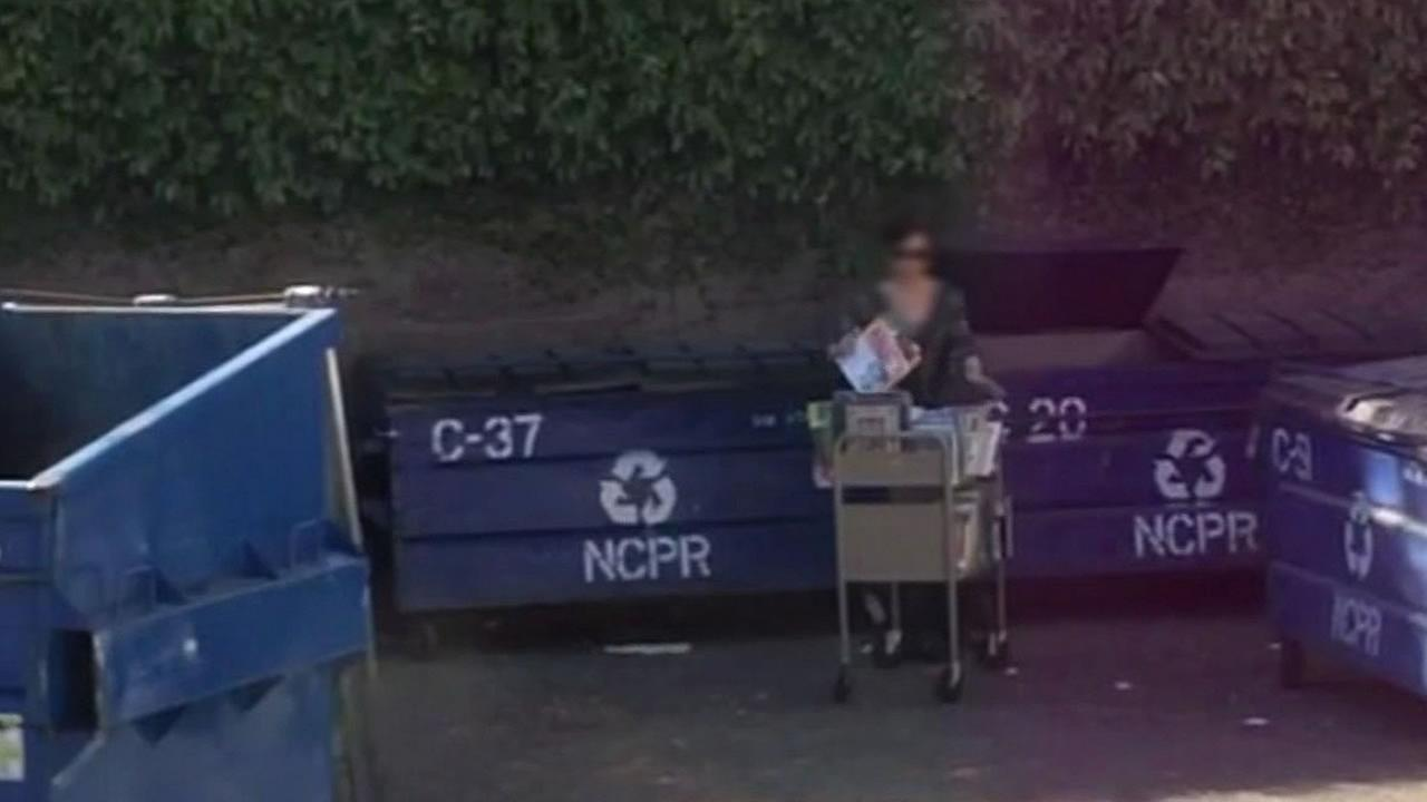 person from the Alameda County Library throwing books in the trash