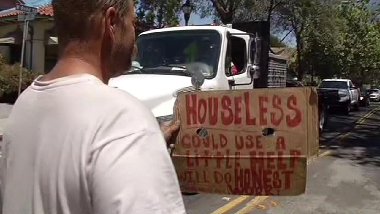File photo - A homeless man holds a sign on the street in San Jose.