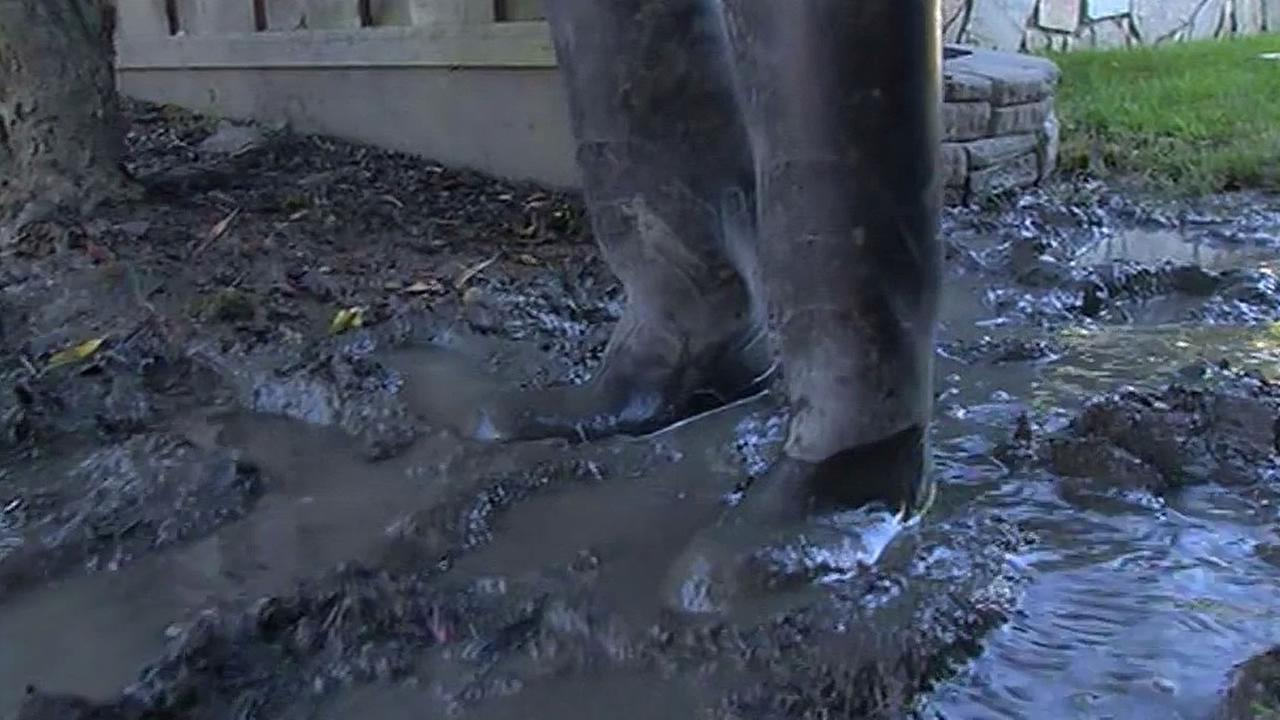 Boots in muddy puddle due to mystery leak