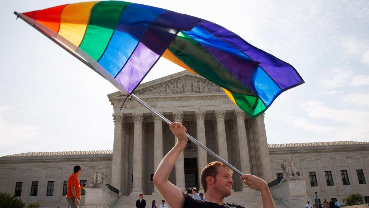 Man waves Rainbow flag outside Supreme Court, Thursday, June 26, 2015.