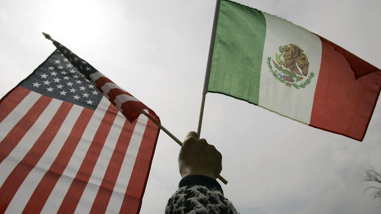 A protester holds up American and Mexican flags during an immigration march and protest in Detroit Thursday, May 1, 2008. (AP Photo/Paul Sancya)