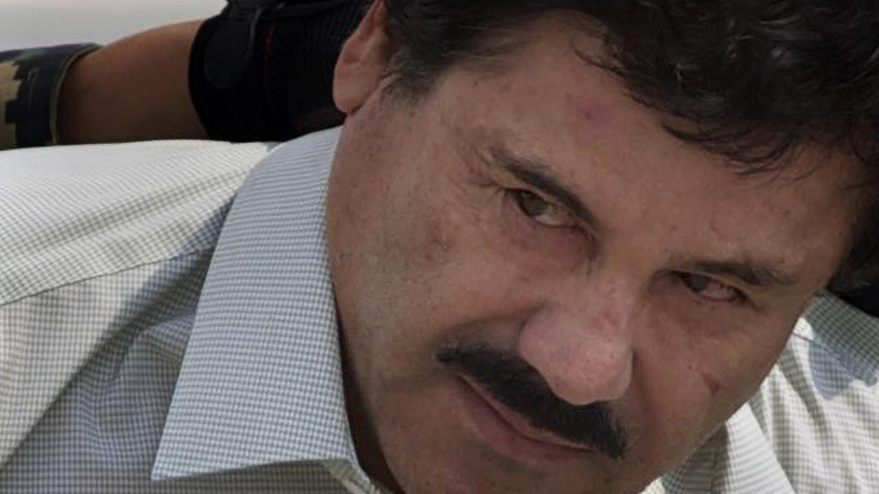 FILE: Joaquin El Chapo Guzman is escorted to a helicopter in handcuffs by Mexican navy marines at a navy hanger in Mexico City, Saturday, Feb. 22, 2014.