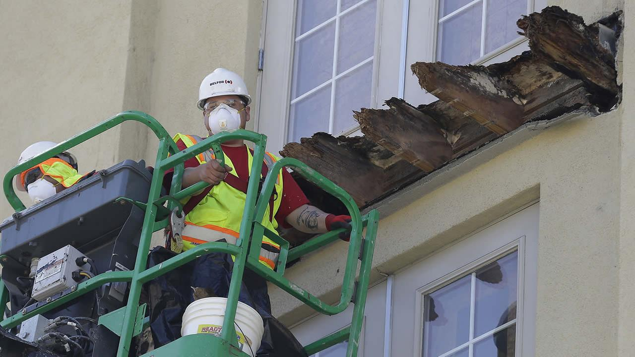 FILE - In this June 18, 2015 photo a crew works on the remaining wood of an apartment building balcony that collapsed killing six college students in Berkeley, Calif. (AP Photo)