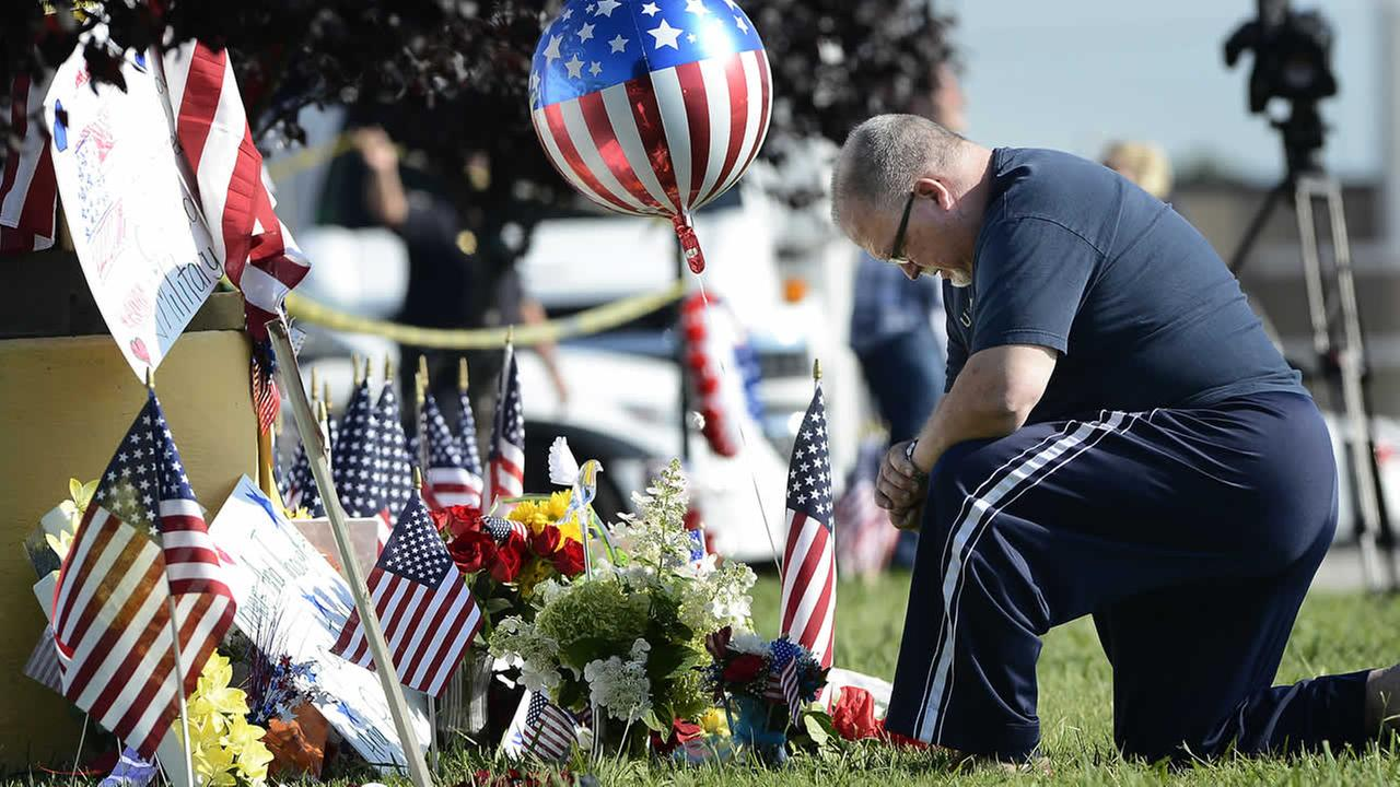 Bill Lettmkuhl kneels by a makeshift memorial in front of near the Armed Forces Career Center on Friday, July 17, 2015, in Chattanooga, Tenn. (AP Photo/Mark Zaleski)