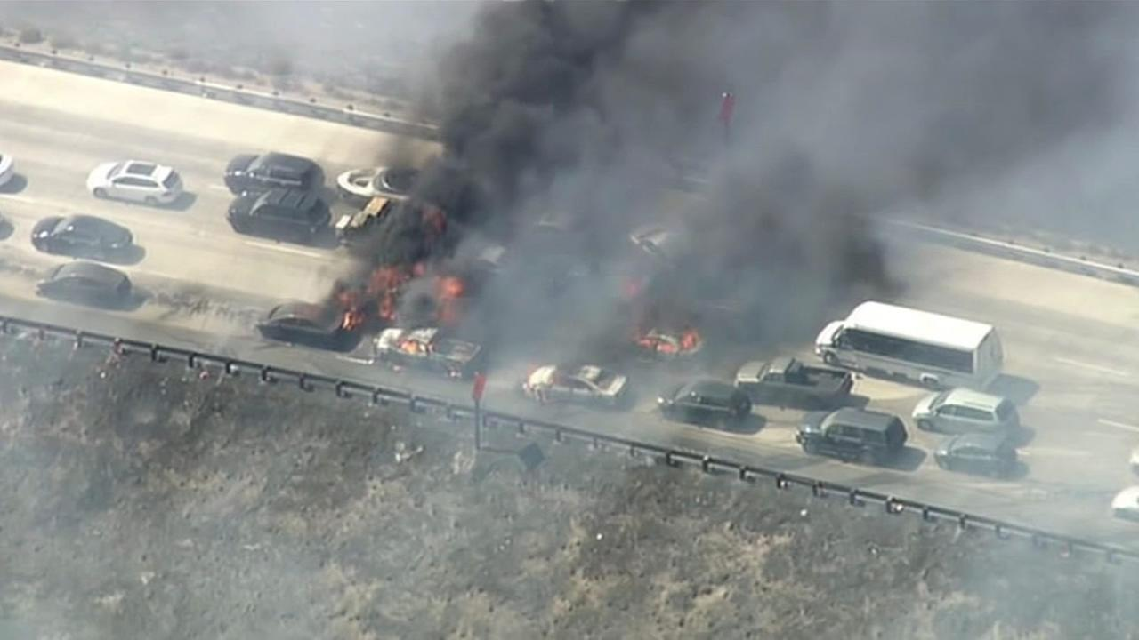 Cars catch on fire while passing through 15 Freeway in Southern California during the North Fire, on Saturday, July 18, 2015.