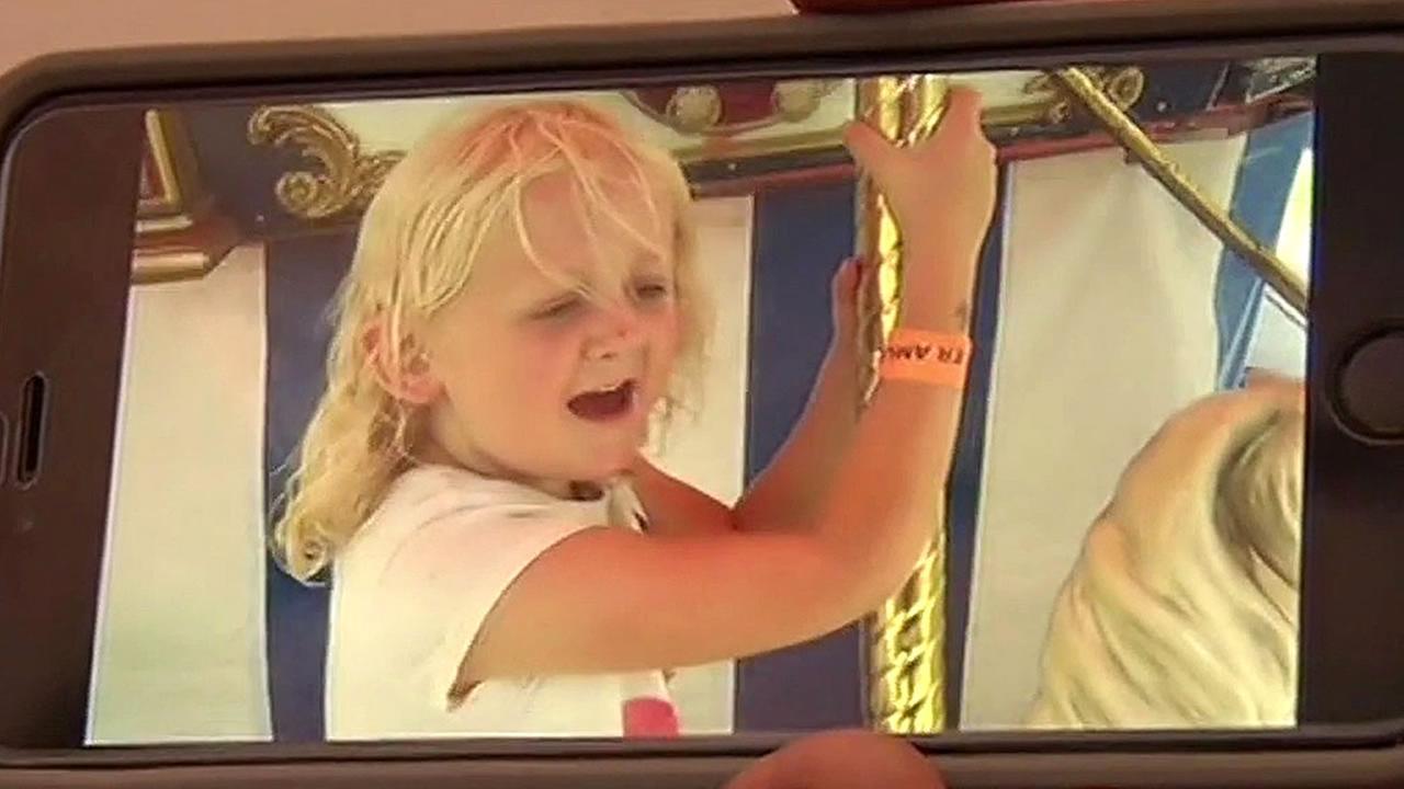 Elizabeth Ripley, 6, rides a merry-go-round
