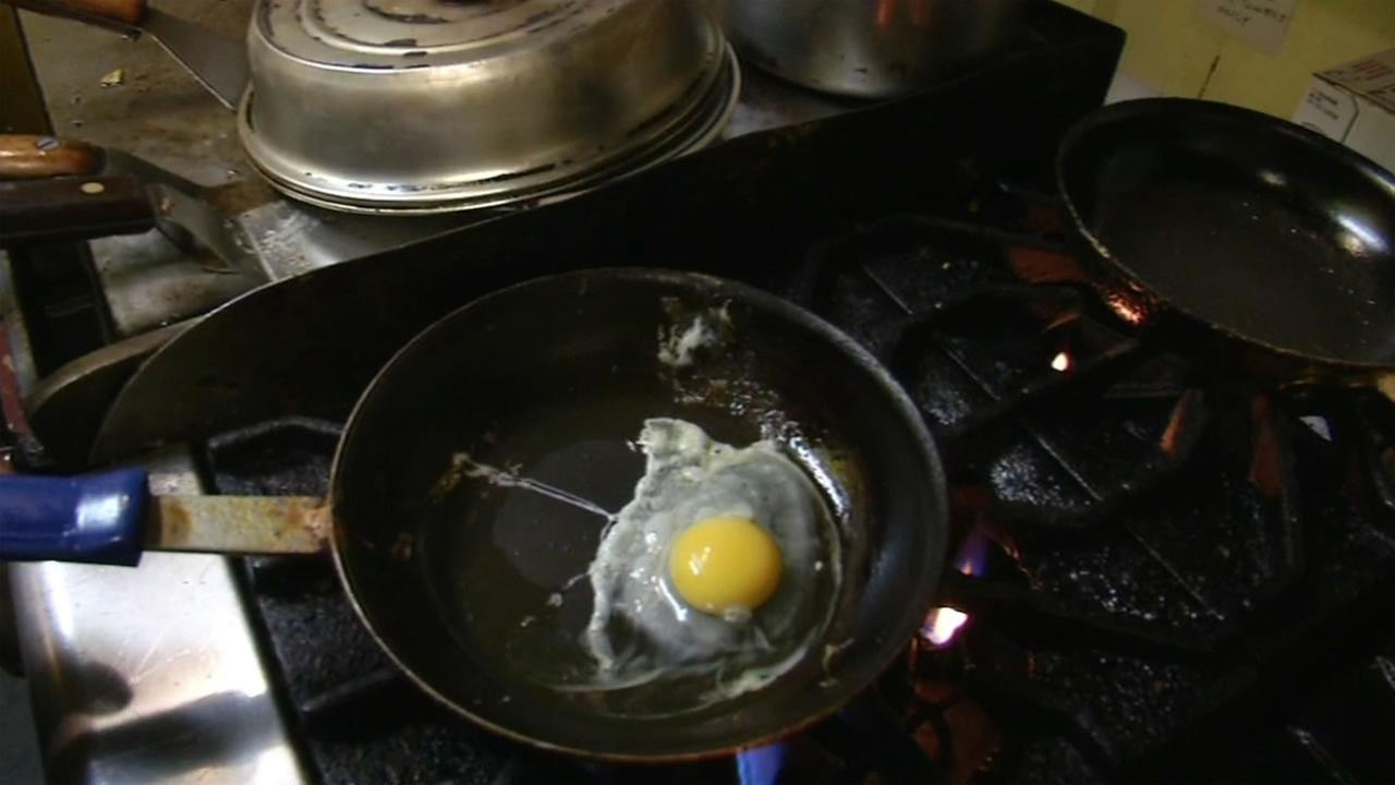 A cook at San Francisco diner Its Tops cracks an egg over a frying pa July 21, 2015,  in the midst of a nationwide egg shortage.