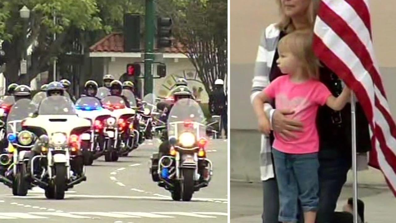 Two-year-old Addie Orcutt and her mother stand on Foothill Boulevard and pay their respects to slain Hayward Sgt. Scott Lunger as his motorcade drives by Thursday, July 30, 2015.