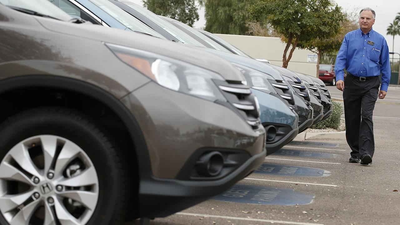 Mike Johnson, a sales manager at a local Honda car dealership, walks past a row of Honda CRV SUVs Tuesday, Dec. 2, 2014, in Tempe, Ariz. (AP Photo/Ross D. Franklin)