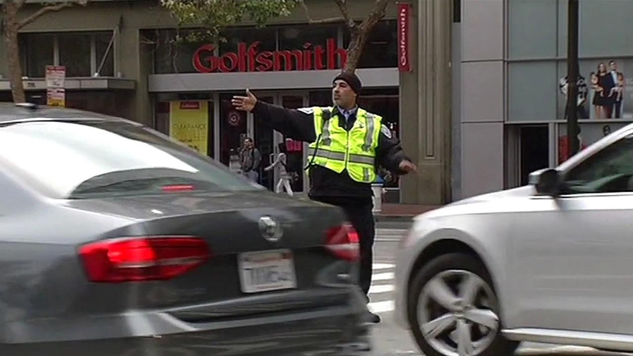 A traffic officer directs vehicles on Grant Street in San Francisco on Tuesday, August 11, 2015.