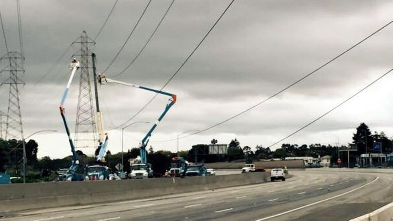 Powerlines are draped over Highway 101 in Burlingame, Calif. as PG&E crews work to repair them on Saturday, August 29, 2015.