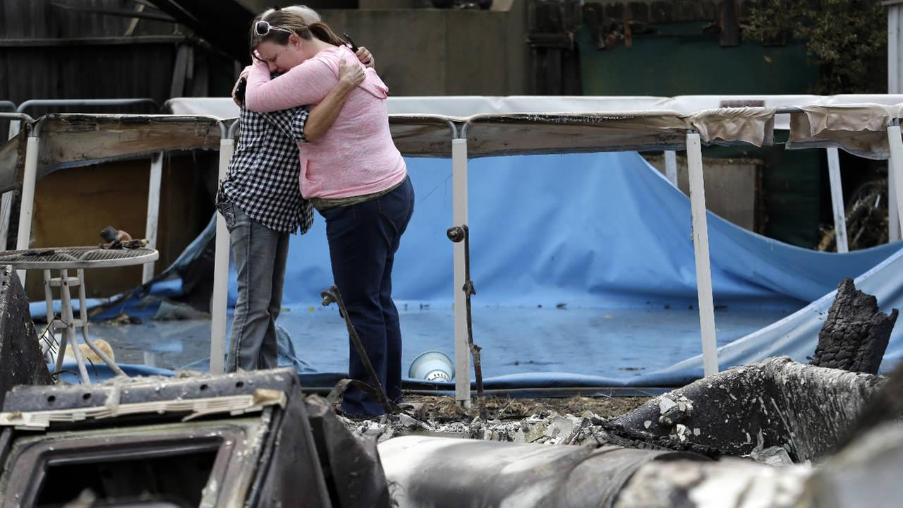Deanna Hingst, right, embraces her mother Shirley Leuzinger as they stand at the familys destroyed home in Middletown, Calif.