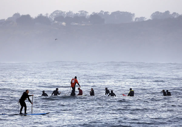 "<div class=""meta image-caption""><div class=""origin-logo origin-image ""><span></span></div><span class=""caption-text"">A man paddleboards, left, past a group of surfers waiting to catch a wave in the first heat of the first round of the Mavericks Invitational big wave surf contest Friday, Jan. 24, 2014, in Half Moon Bay, Calif. (AP Photo/Eric Risberg) (AP Photo/Eric Risberg)</span></div>"