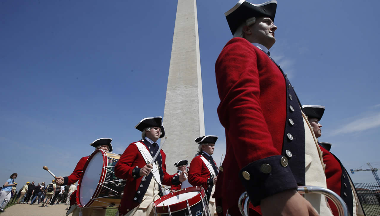 Members of the United States Army Old Guard Fife and Drums Corps march beneath the Washington Monument in Washington, Monday, May 12, 2014. (AP)