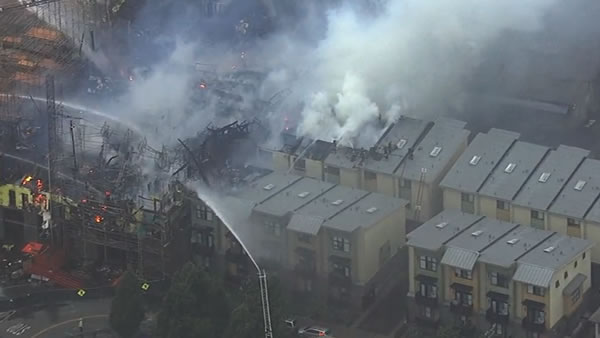 <div class='meta'><div class='origin-logo' data-origin='none'></div><span class='caption-text' data-credit='KGO-TV'>The 6-alarm fire burning in Emeryville, Calif. spreads to nearby townhomes on Wednesday, July 6, 2016.</span></div>